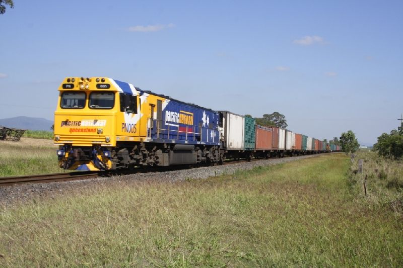 A modern diesel locomotive hauls a load of containers near Sarina on the North Coast Line.